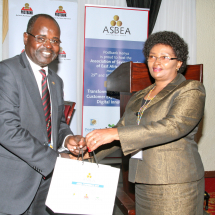 Dr. Habil Olaka, CEO Kenya Bankers Association (KBA) receives a token of appreciation from Ms. Anne Karanja, Managing Director